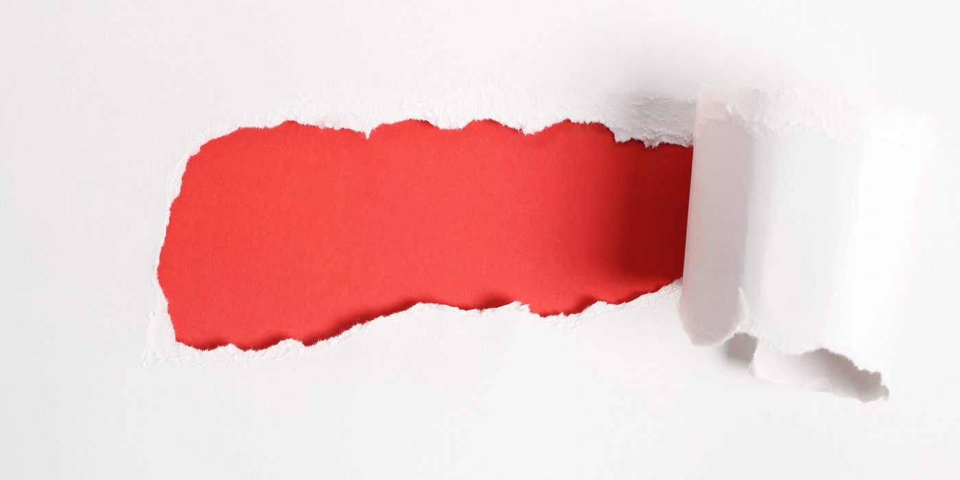 Concept. Torn paper with red background